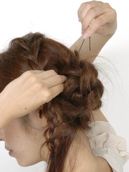 編んである毛束を少量すくい、毛束と頭部の髪をからませてアメピンでとめる 編んである毛束を少量すく