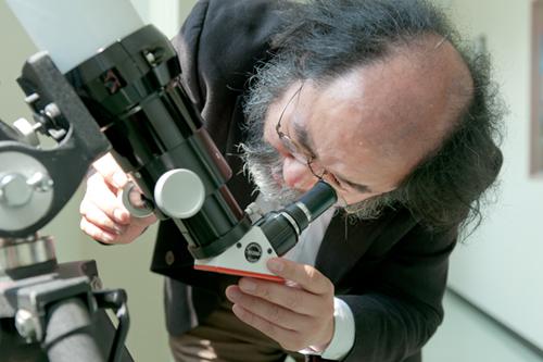 望遠鏡を覗く大西教授
