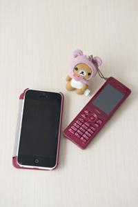 携帯は、仕事と家庭用で使い分けている。子どもとの連絡用の携帯(右)には子どもが好きなキャラクターをつけて